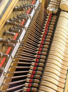 دمپرها در بخش باس یک پیانو دیواری همانطور که در میانه تصویر مشاهده می کنید دمپرها روی سیم ها را پوشانده اند