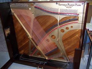 تصویری از بخش داخلی یک پیانو دیواری - ساند بورد، صفحه چدنی، سیمگیرها و سیم ها در عکس کاملا مشخص می باشد